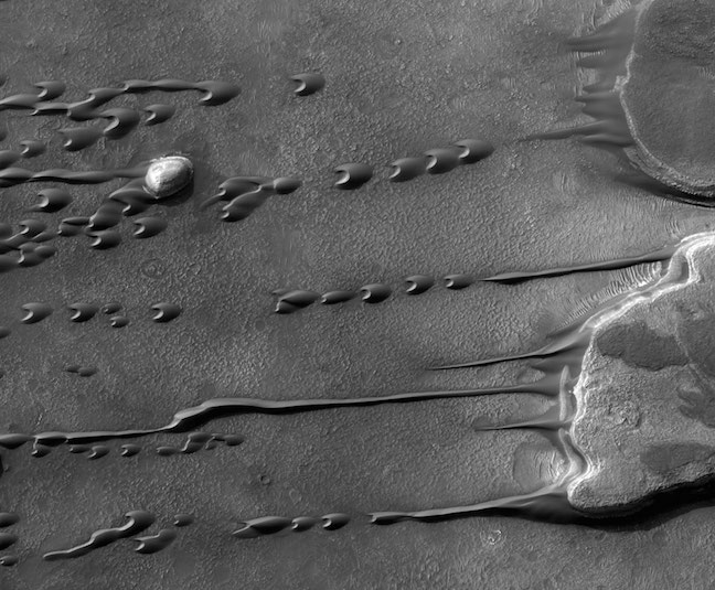 Although liquids freeze and evaporate quickly into the thin atmosphere of Mars, persistent winds may make large  sand dunes appear  to flow and even drip like a liquid. Visible on the  above image  right are two flat top mesas in southern Mars when the  season was changing  from Spring to Summer. A light dome topped hill is also visible on the far left of  the image . As winds blow from right to left, flowing sand on and around the hills leaves  picturesque streaks . The dark arc-shaped  droplets  of fine sand are called  barchans , and are the interplanetary cousins of similar Earth-based sand forms.  Barchans  can move intact a  downwind  and can even appear to pass through each other. When seasons change,  winds on Mars  can kick up dust and are  monitored  to see if they  escalate  into another of Mars' famous planet-scale  sand storms .