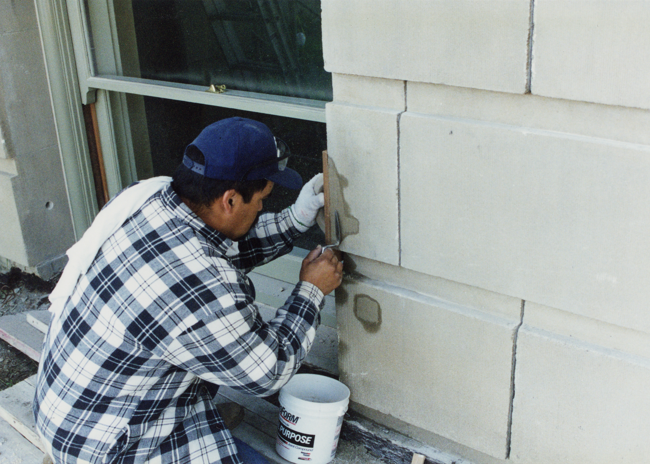Workman blending patch materials during repairs to precast concrete.jpg