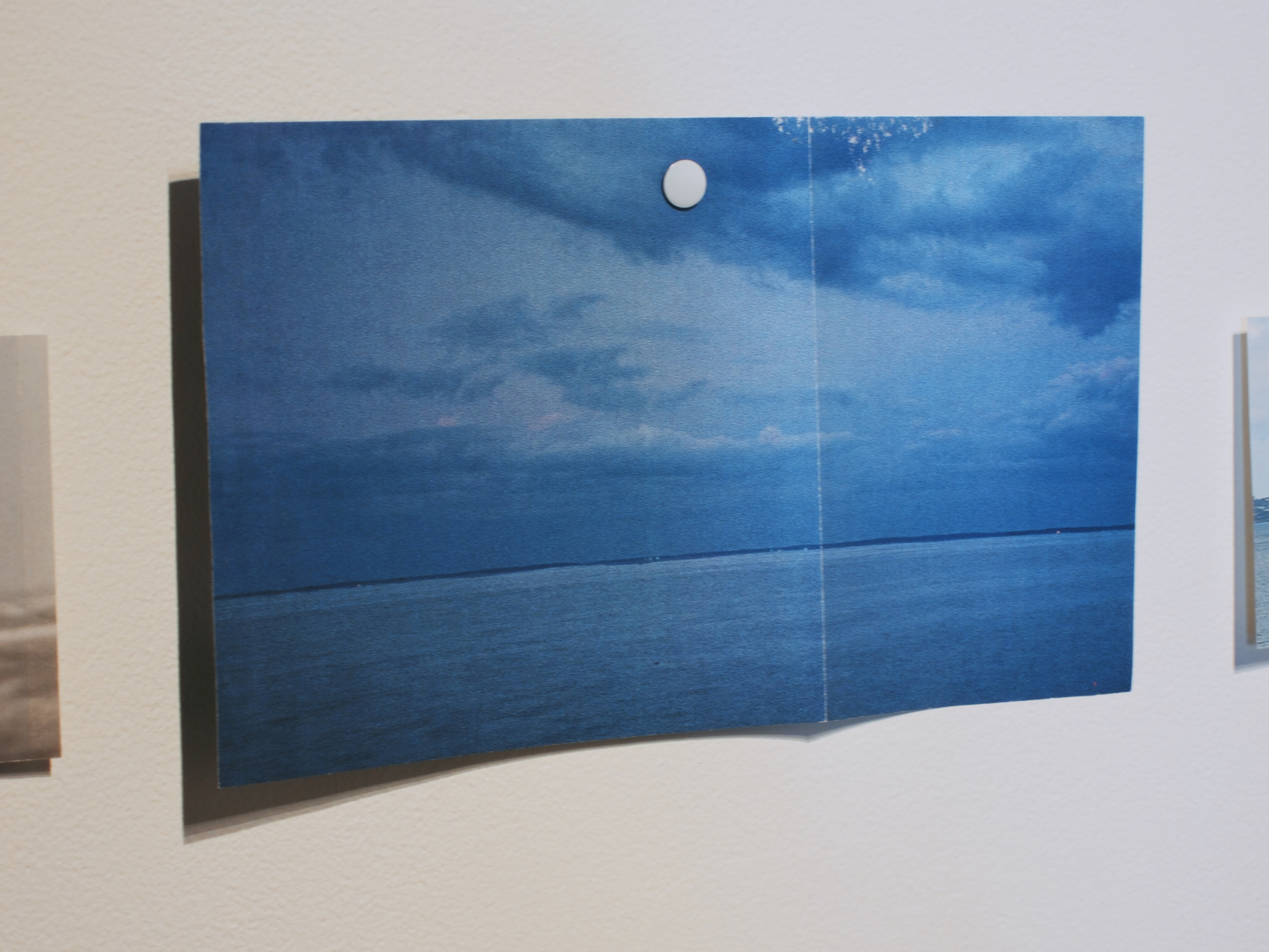 Cut out National Geographic image of ocean horizon pinned to the wall, 2014.