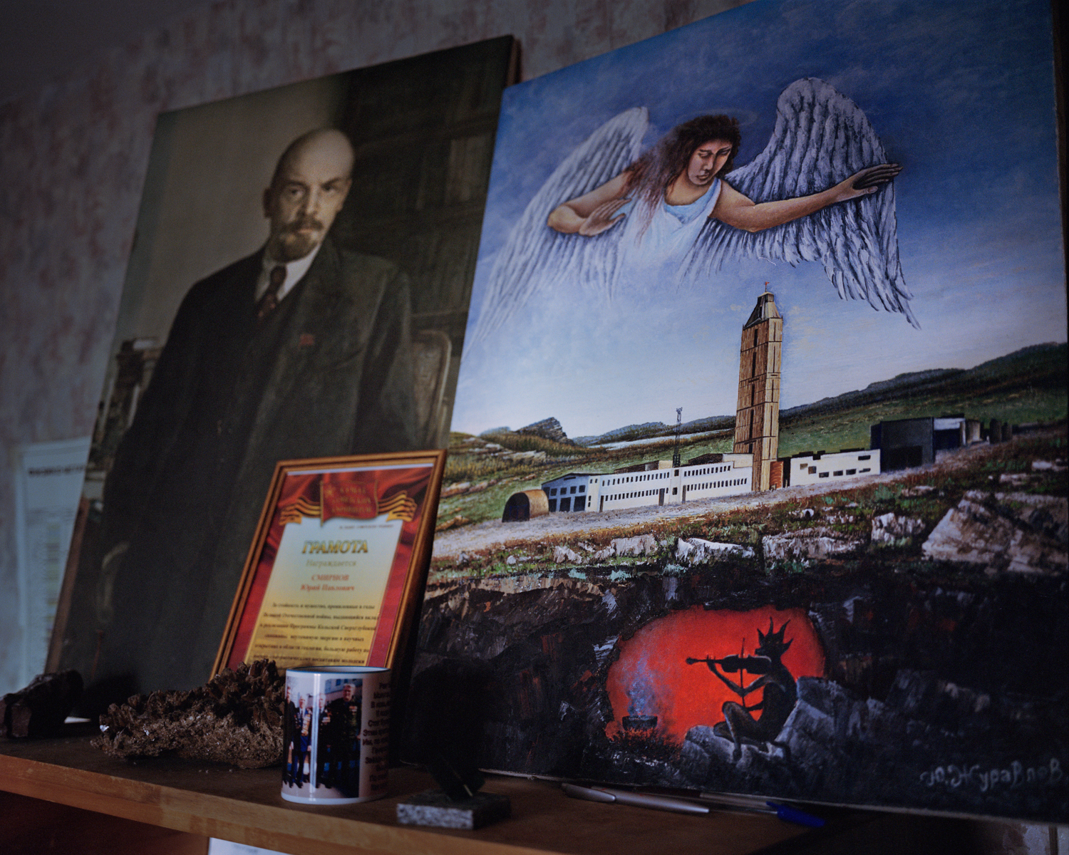 Smirnov displayed a portrait of Lenin, left, next to a painting depicting the urban legend that the sounds of hell could be heard coming from the bottom of the borehole.