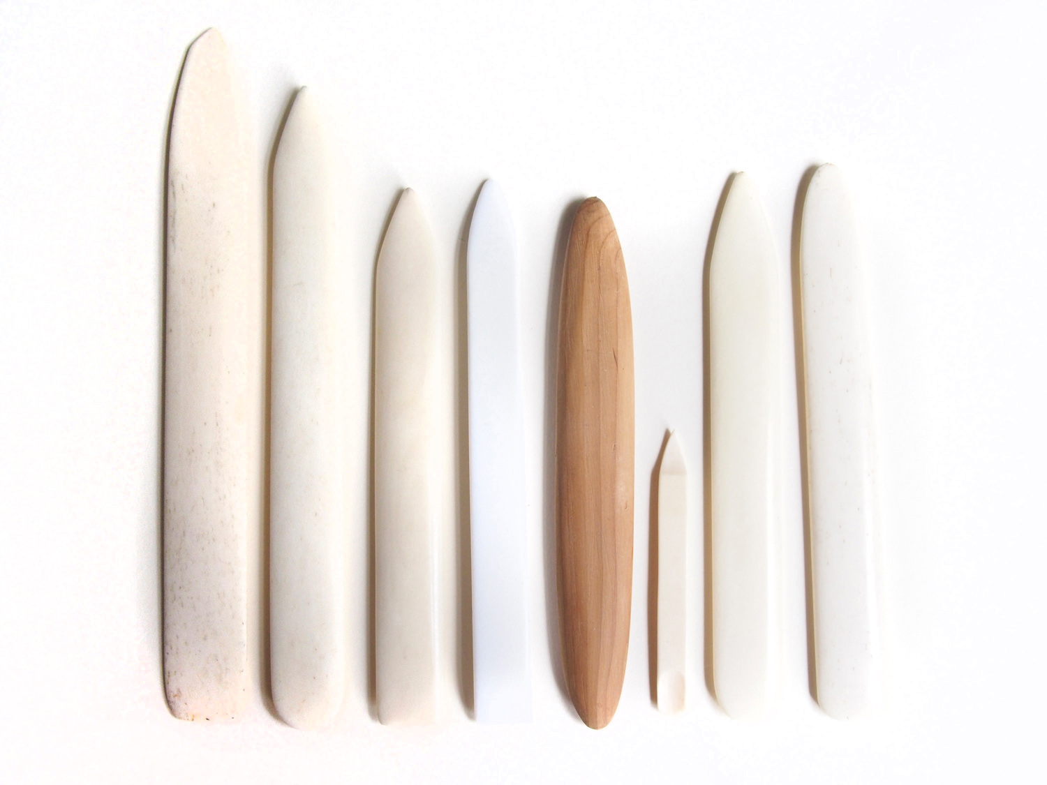 More bone folders than I need: I only ever use the one to the left of the PTFE (white) one, and the tiny one. Tiny one came from a manicure set, and has a little curve at the tip. The wooden one is a replica 18th c. French folder that Tristram made me.