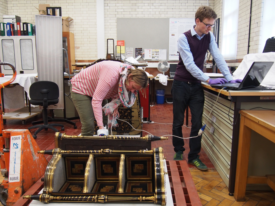 Dana and Tristram looking at a pair of 18th century French side tables