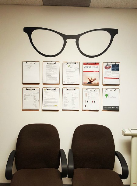 An office space created and organized featuring our cat eye glasses wall decal. Photo credit: Missy - Walman Optical.