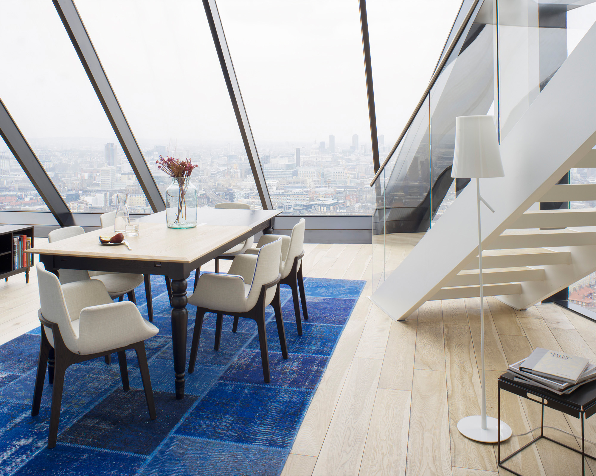 Dining table overlooking London in one of its highest apartments, dining chairs are Poliform, the table is an extension table by Georg Œhler manufactured in London.  Photography Justin Barton