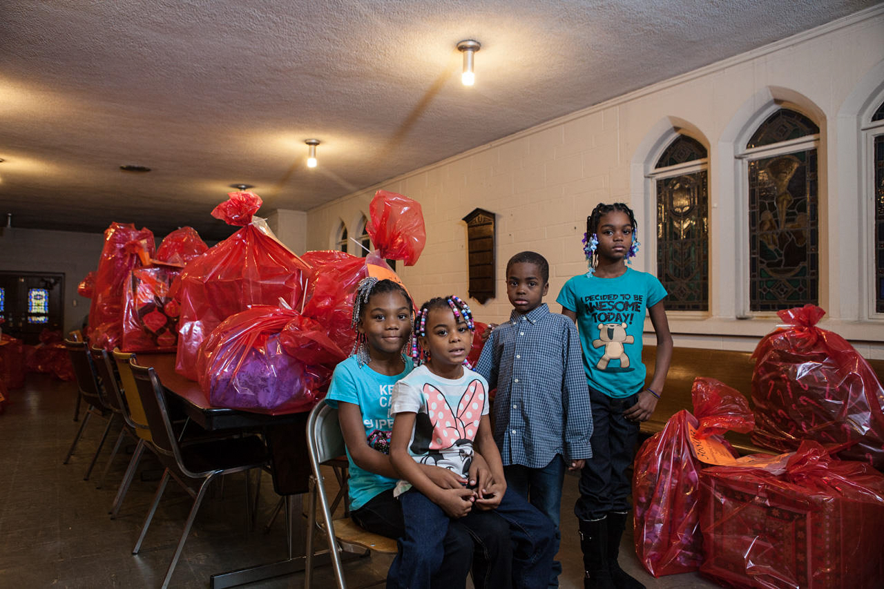Shaniah, Natialya, Ariya, and Martiese Brown receive donated gifts for Christmas at Peace Lutheran Church in the Morningside neighborhood.