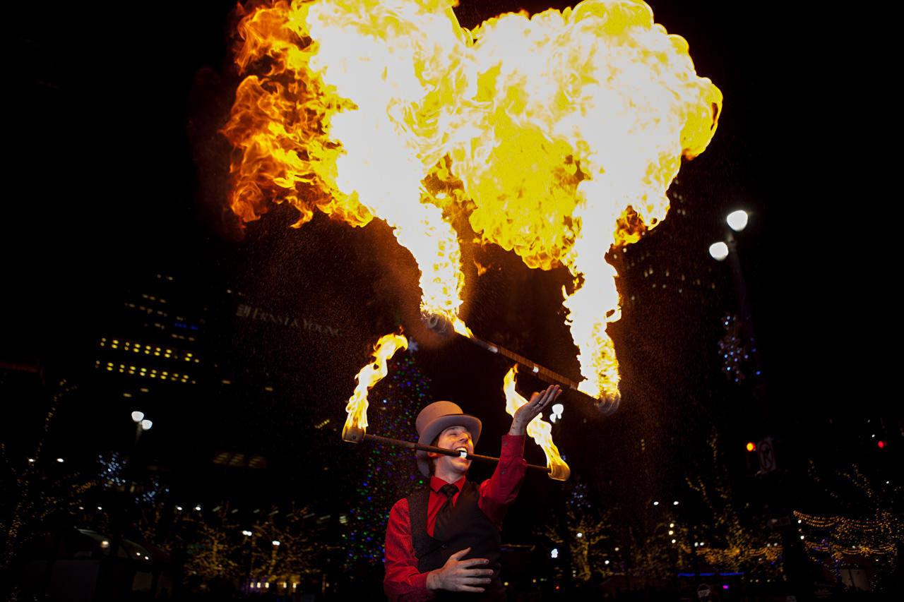 Andrew D'Ascenzo, a performer for Bacchanal Promotions, throws fire at Campus Martius Park.