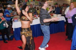 """The theme of the day was a """"world tour"""" andthe company provided entertainment fromaround the globe including an """"OompahBand"""" from Germany, a duo of Irish singersand an exotic belly dancer who engagedseveral of the attendees"""