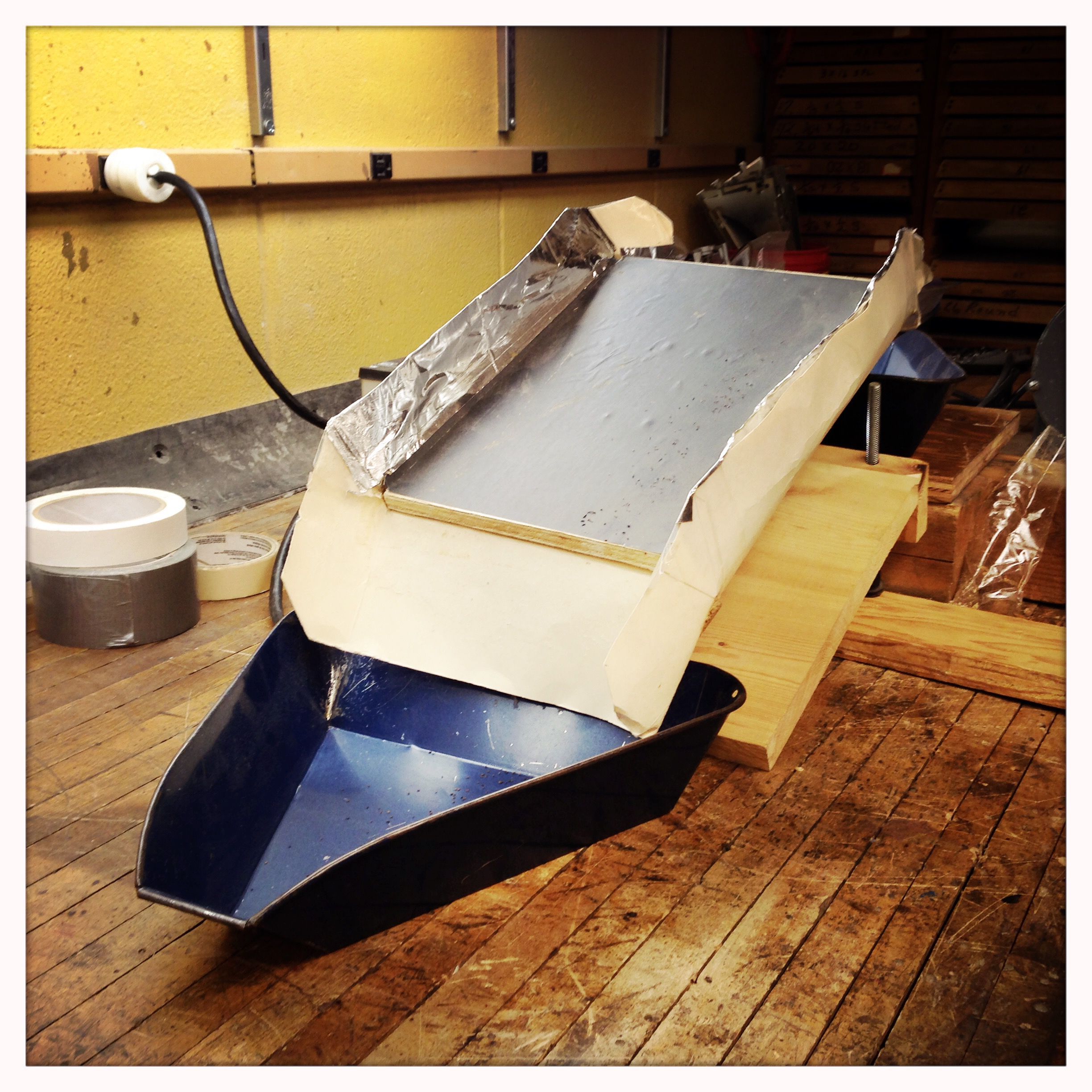 Makeshift vibratory deck separator (design by Alan Gaul). Easily-rolling objects, such as round seed, collect down into the lower blue tray while remaining objects vibrate upwards over the plate.