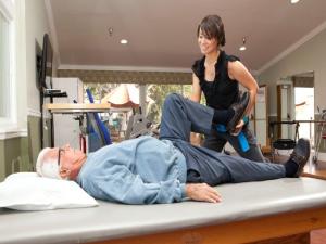 Rehabilitation staff member, bending patient's knee.
