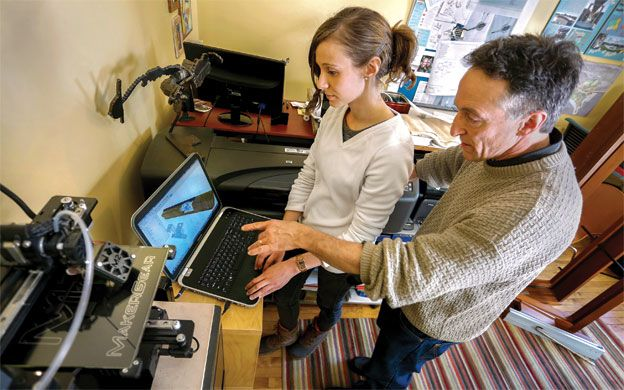 Patric Santerre  (right), architect and industrial designer at ARCADIA designworks, and intern Anya Timchenko prepare data so a  MakerGear M2 printer  can create a window lock mechanism.