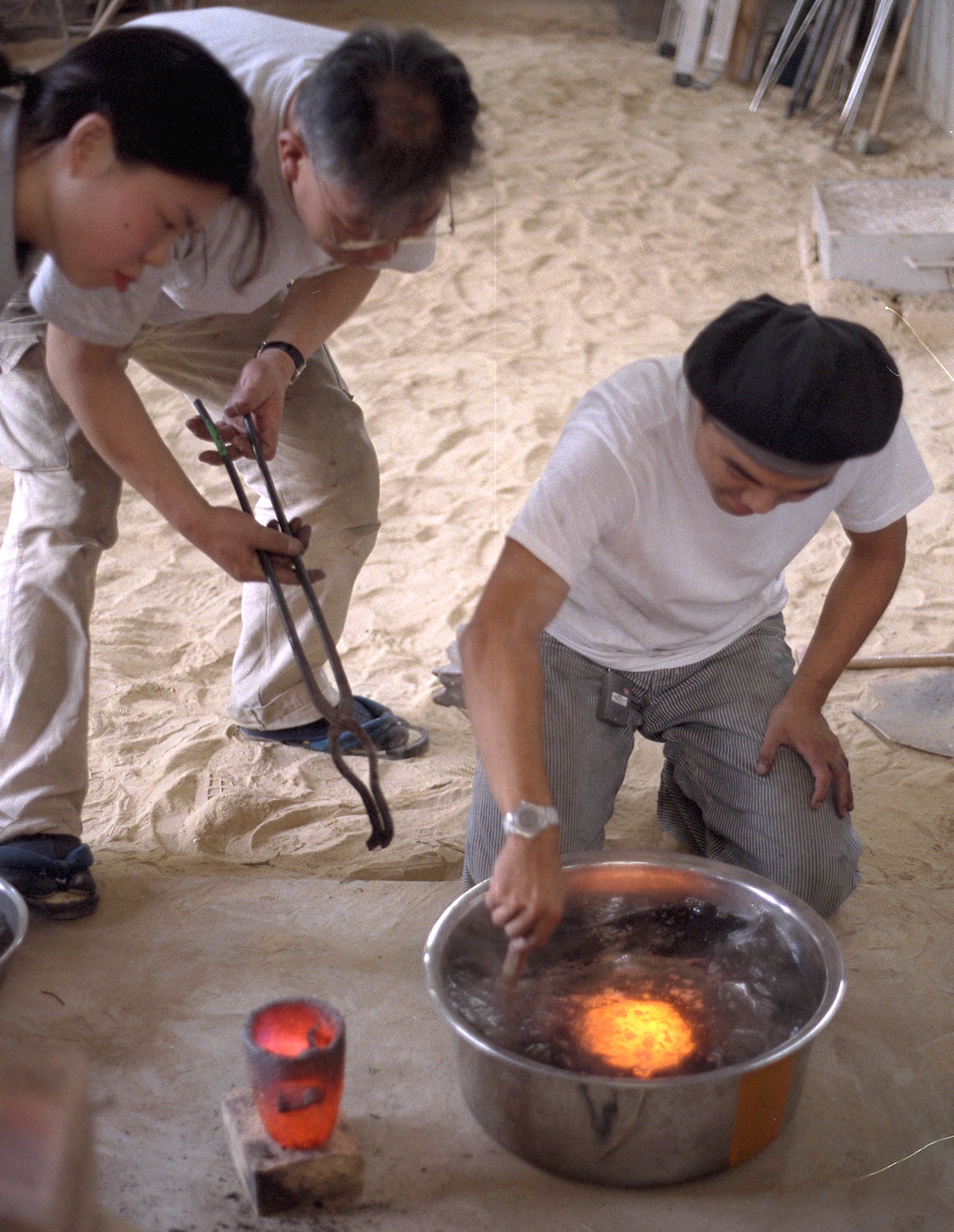 5: The metal, though still molten, does not burn the cloth because a jacket of steam forms around the metal. After pouring, the water is stirred around the molten metal to hasten quenching.