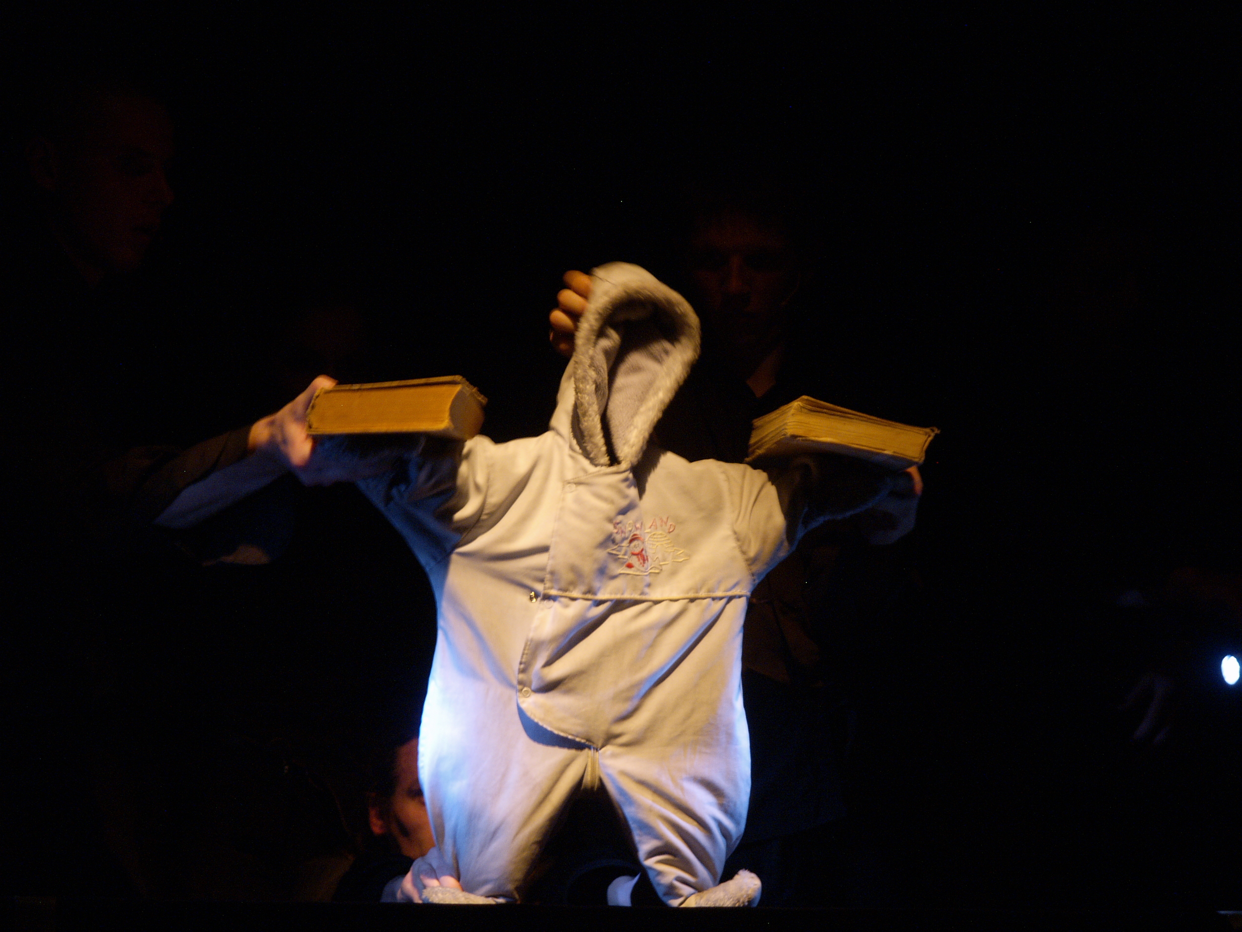 An empty snowsuit is transformed into a contemporary everyman on a dark odyssey through the 20th century. Based on a comic strip, this award-winning collaboration by avant-garde Slovene physical theater troupe Betontanc, Latvian object theater masters Umka. lv, and the Slovene pop-electronic group Silence,  Show Your Face!  combines puppetry, physical and object theater, and live music for a truly virtuosic performance.   Photo Credit: Gints Malderis