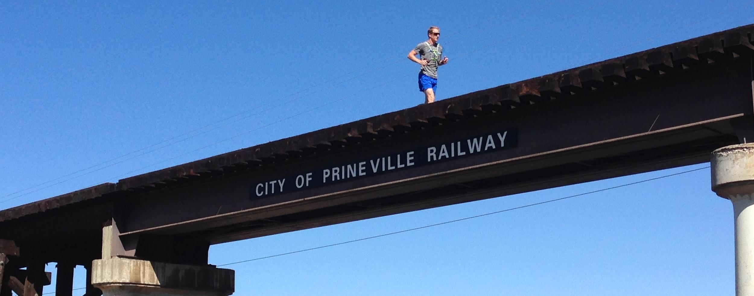 Adam running across railroad bridge, entering Prineville, July 2014