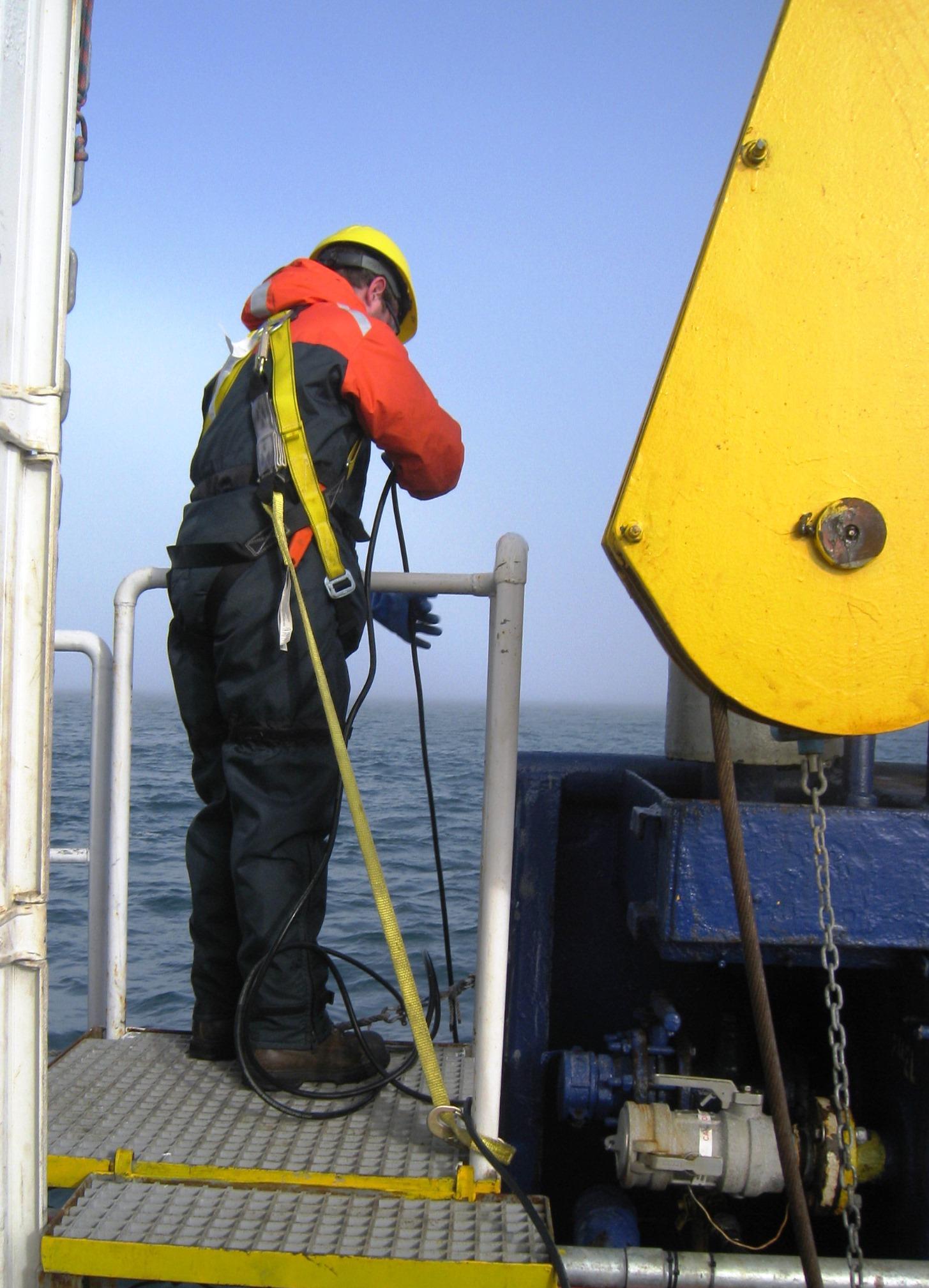 JASCO field scientist deploying the hydrophone of the OSM underwater sound level meter