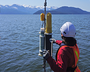 Ocean bottom hydrophone being prepared for underwater acoustic measurements by JASCO field scientist