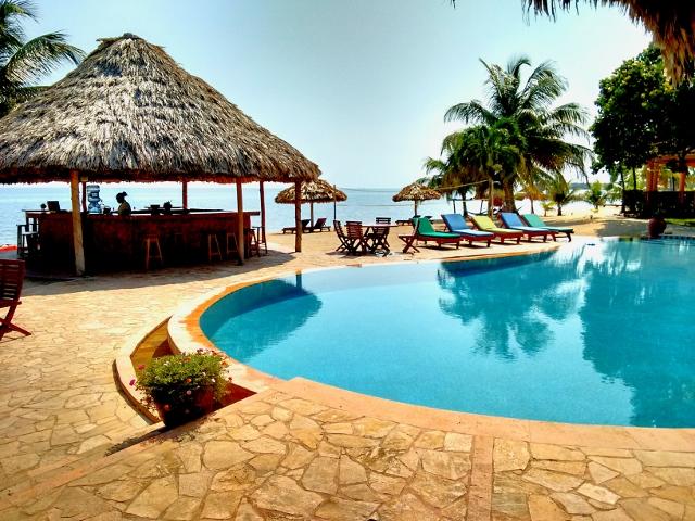 the pool and beach bar at belizean dreams resort overlooking the caribbean sea in hopkins, Belize