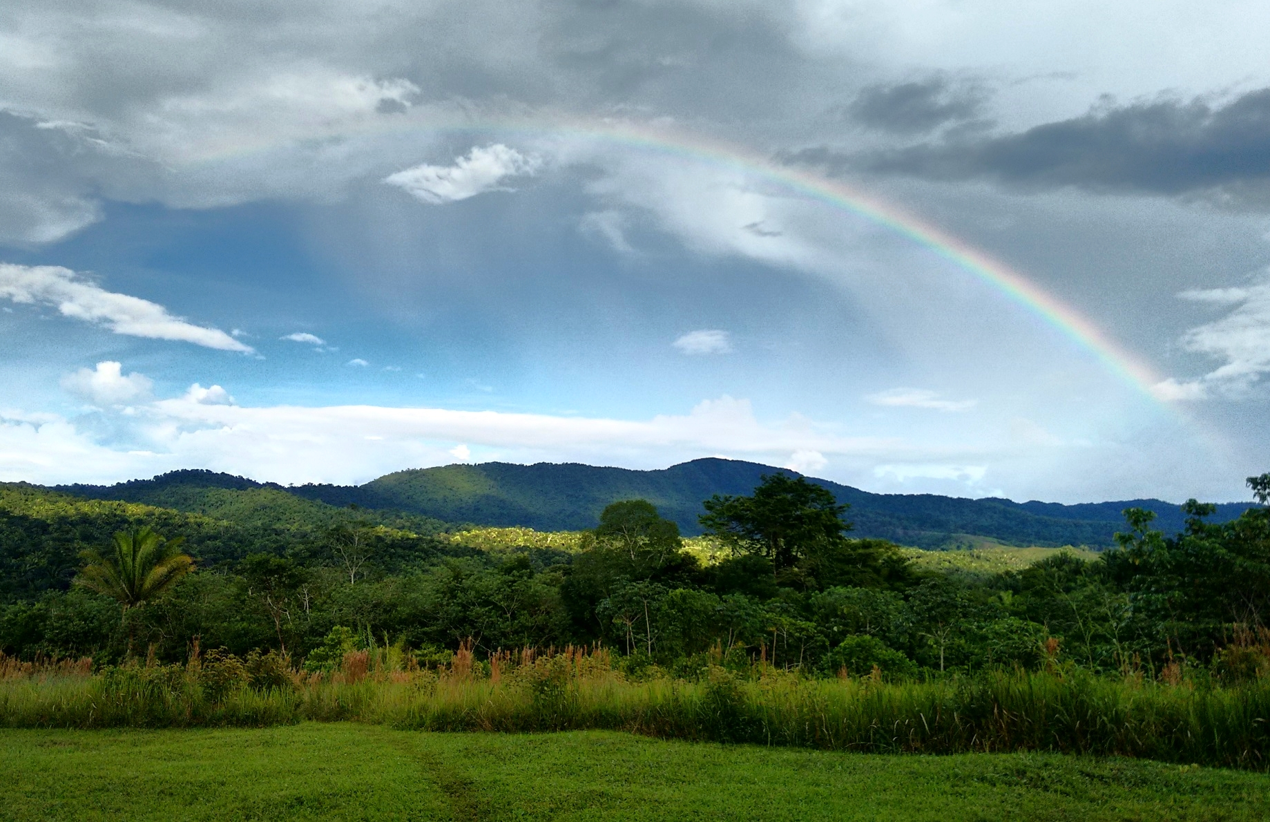 A rainbow stretches above the Jungle covered hills at the headquarters of SabreWing Travel on the Hummingbird Highway in Belize