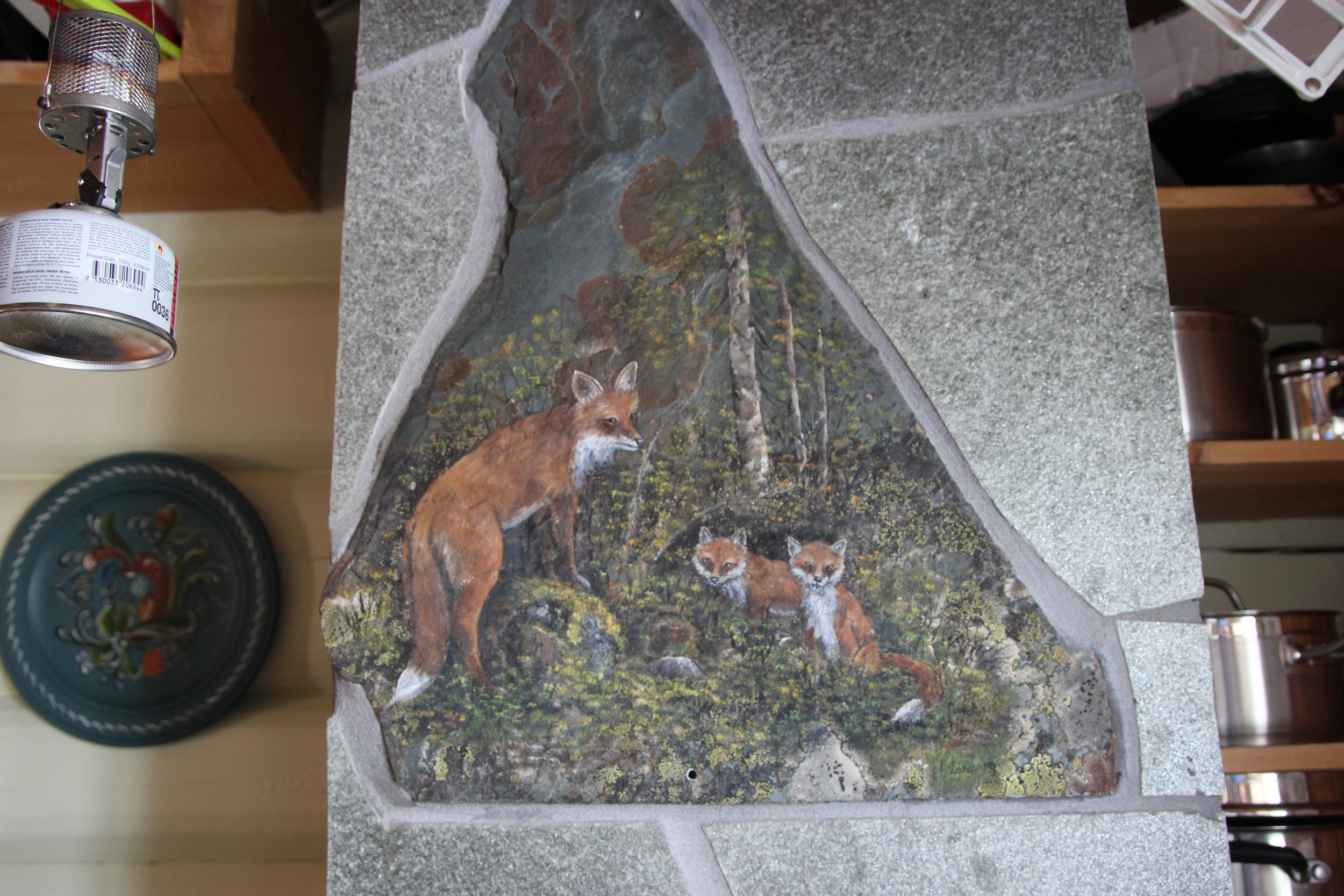 A pack of fox hand painted on tile with lichen growing in.