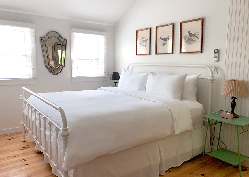 white bed with green nightstand