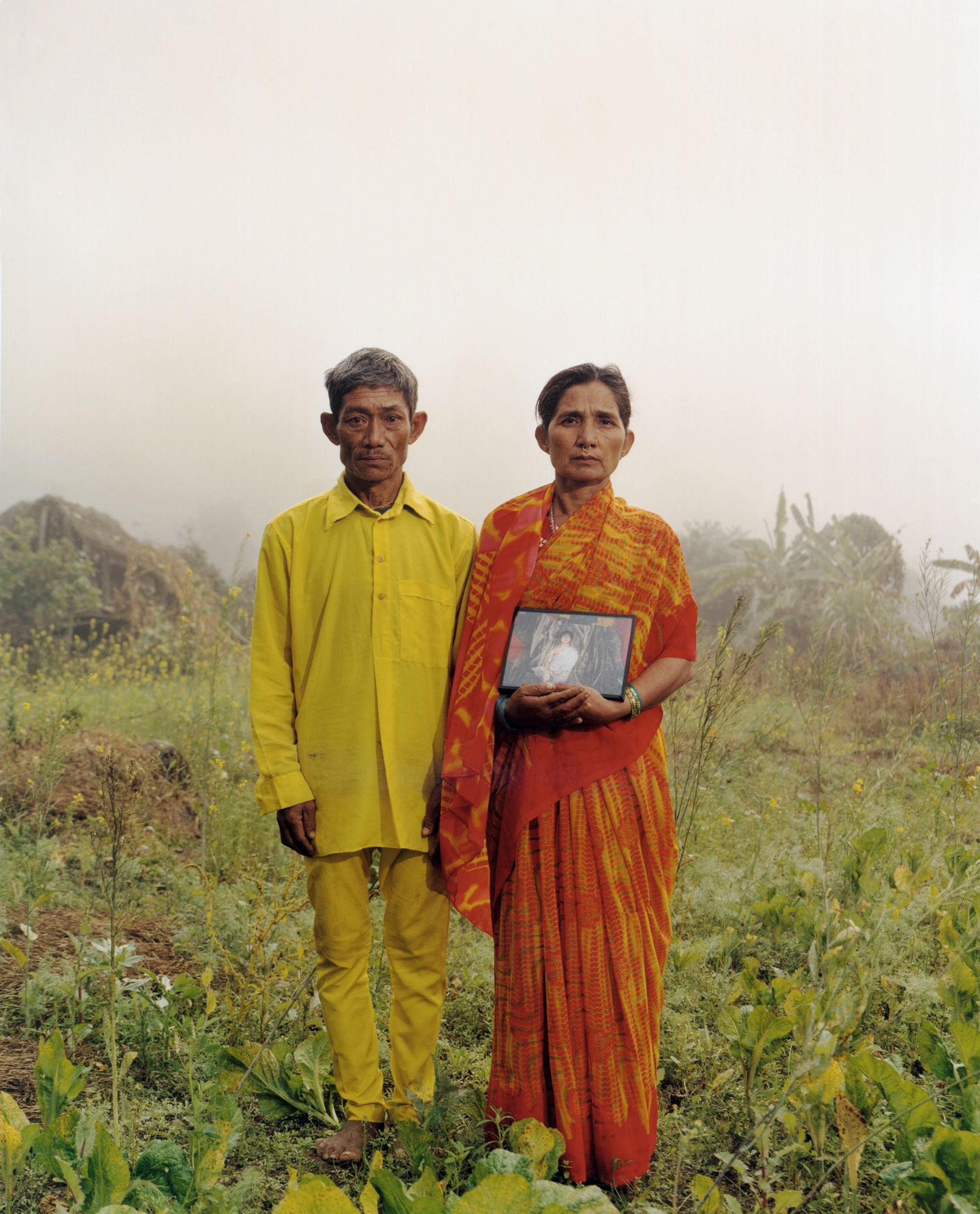 """The parents of the """"Buddha Boy"""" holding a photo of their son - Bara Region, Nepal, 2006"""