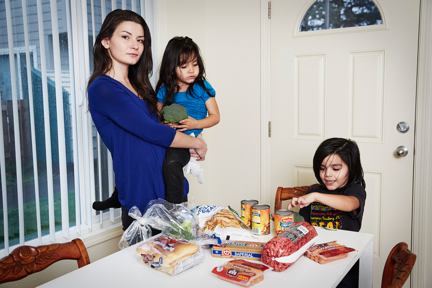 Jennifer Noonan works part-time for Walmart and is pictured here with the food she was able to buy at the end of the month (with about $20 left to her name), including a couple of packs of hotdogs, margarine, canned chili and broccoli. She shops at a Grocery Outlet, a discount store near her home to save cash.