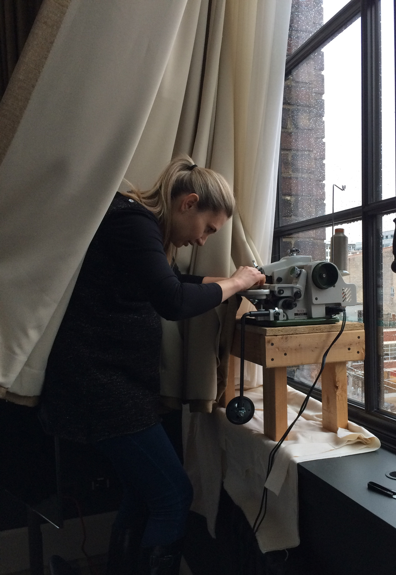 A Primo team member on-site at  Soho House Chicago , on-site blind-hemming a pair of drapes that stretched for the perfect length.