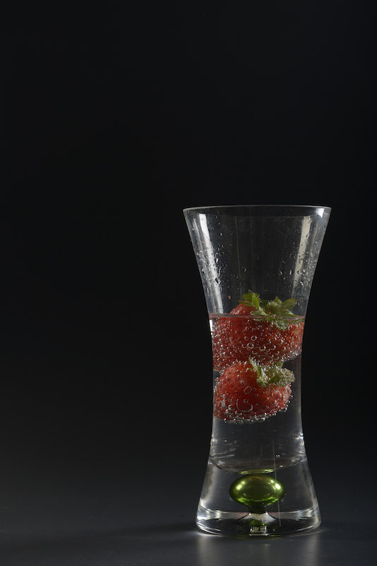 A glass vase filled with soda and strawberries sits in front of a solid black cardboard backdrop as part of a glass work project completed October 3, 2014. Soft boxes sit on either side of the object with a snoot above the vase to light the rim.