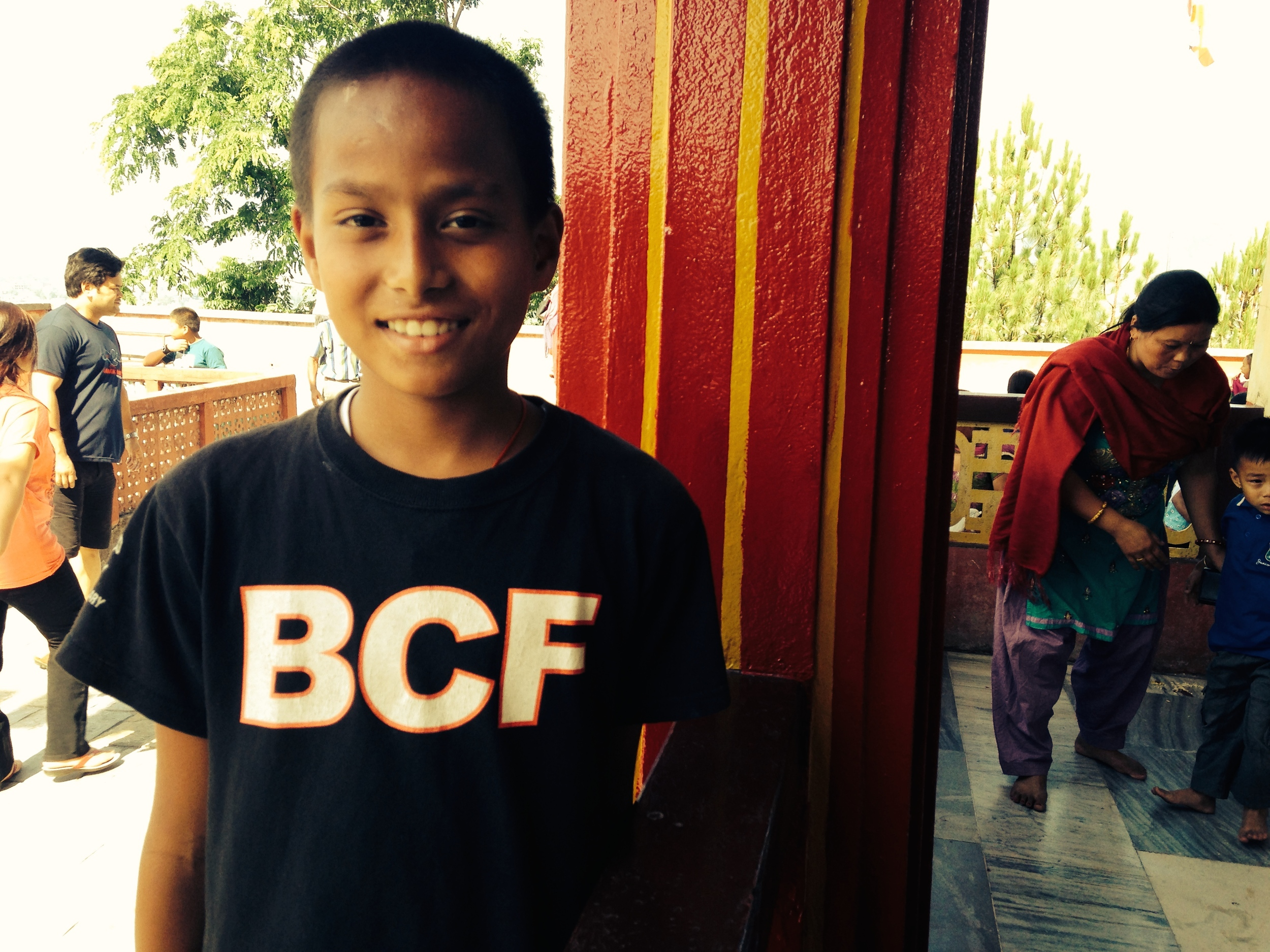 A smiling student proudly sports his  new t-shirt  from a football club in Colorado, U.S.A.