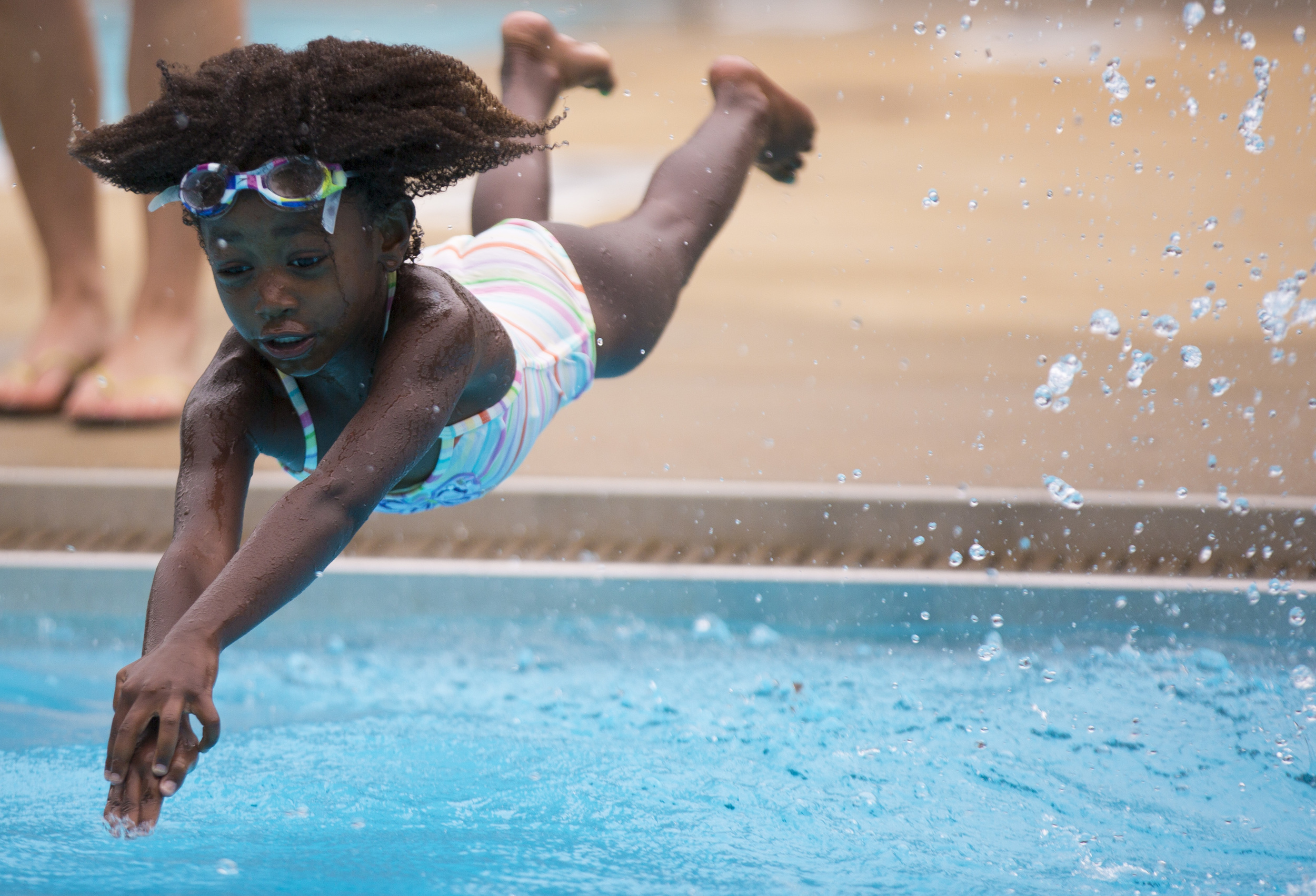 Eloise Sayre, 5, dives into Ridge Road Pool in Raleigh Friday, July 11, 2014. Sayre loves coming to the pool to cool off and play with her friends.