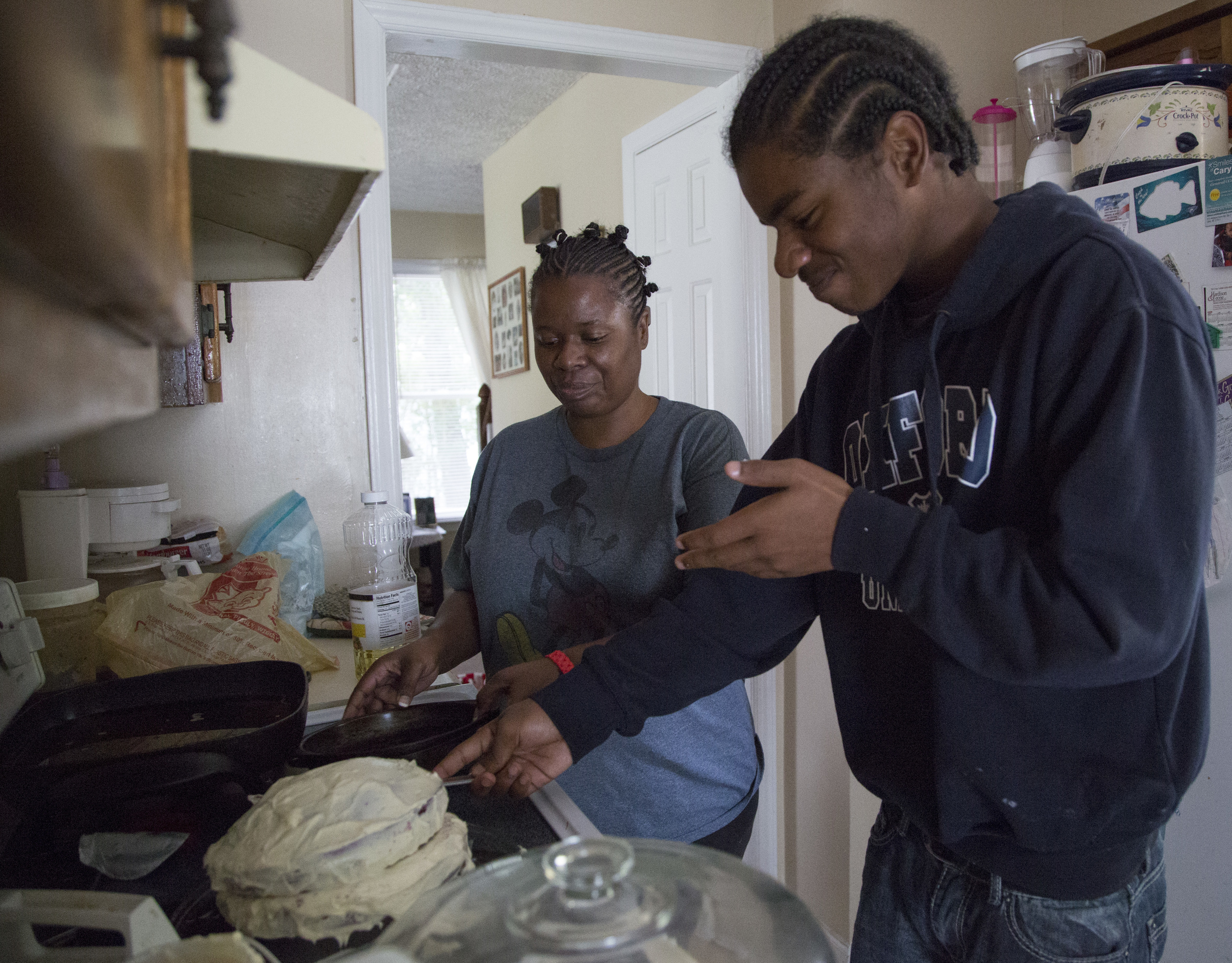 Monica Alexander helps her son, McKinley Patterson, 14, make his birthday cake at their home in Zebulon, N.C., on Wednesday, July 23, 2014.