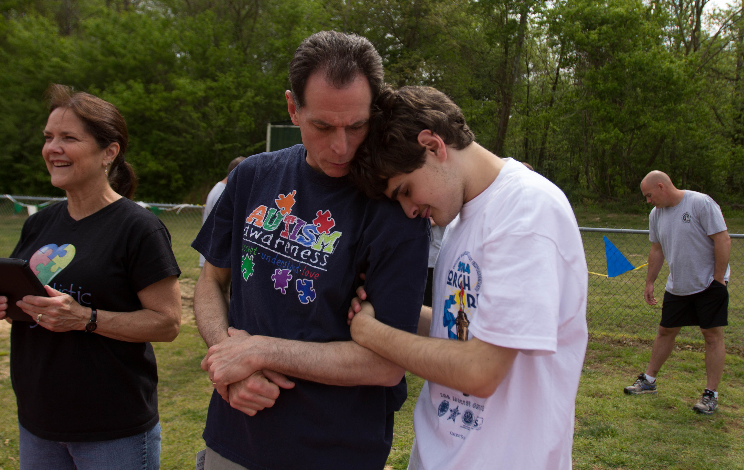 """""""Everything was fine. He was right on cue with everything. He even had some words,"""" said Vicki Gurganus. """"But then at about 18 months, he stopped paying attention when we said his name.""""  Her son, Zackary """"Zack"""" Gurganus, now 16, was diagnosed with autism at 22 months.  Autism is a developmental disorder that is usually diagnosed within the first five years of a child's life. It affects the neurological development of social and communication skills, but it is still unknown whether the autism is caused by genetics or early childhood environment. Regardless of its cause, autism is life changing.  While waiting for the Special Olympics Spring Games to begin, Zack clings to his father, Kevin Gurganus."""