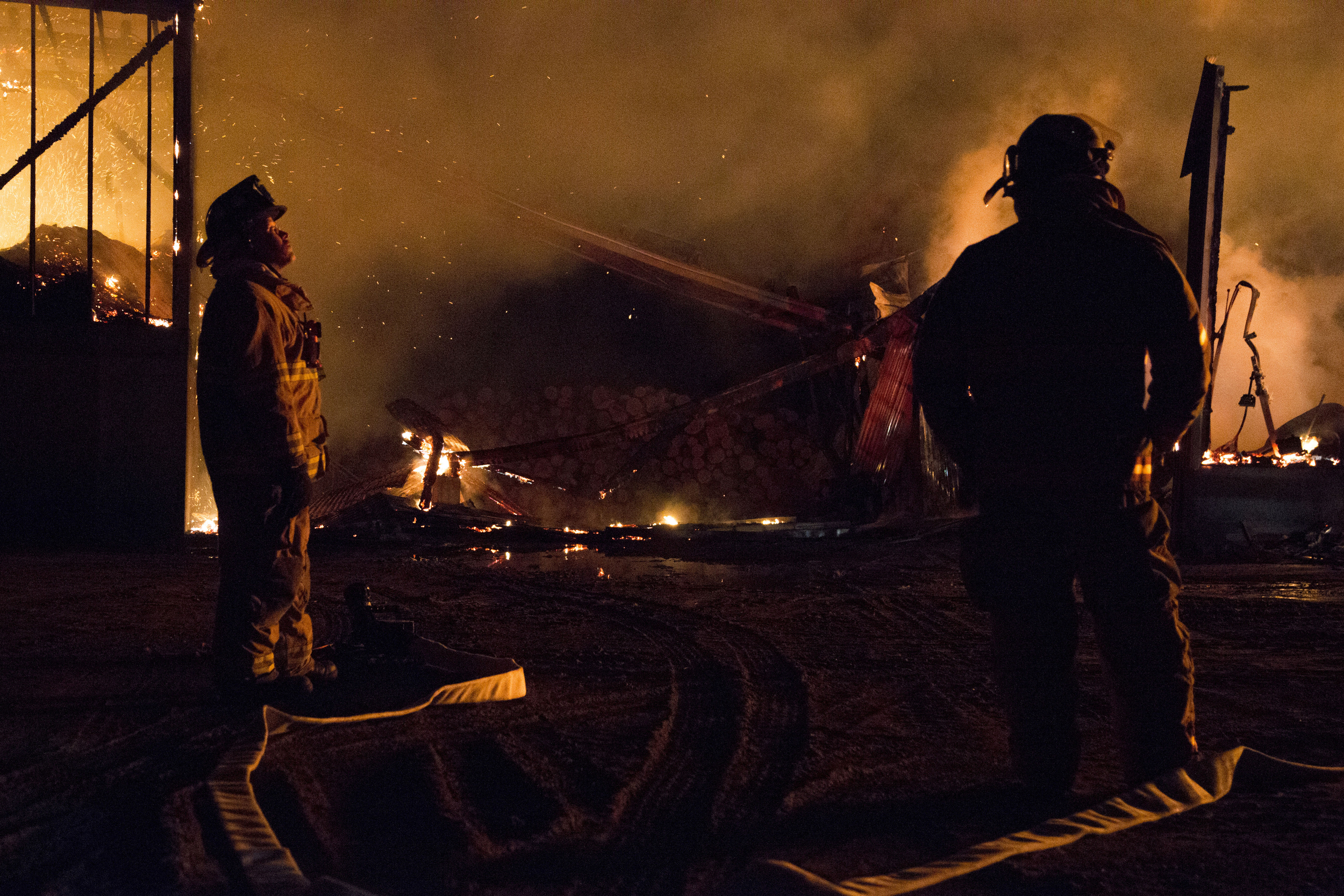 Hartford firefighter Zach Bowley, left, and Fairlee firefighter Geoffrey Mallett watch as firefighters from across the Upper Valley fight to put out a four-alarm fire at Britton Lumber Co in Fairlee, Vt., on Saturday, March 28, 2015.