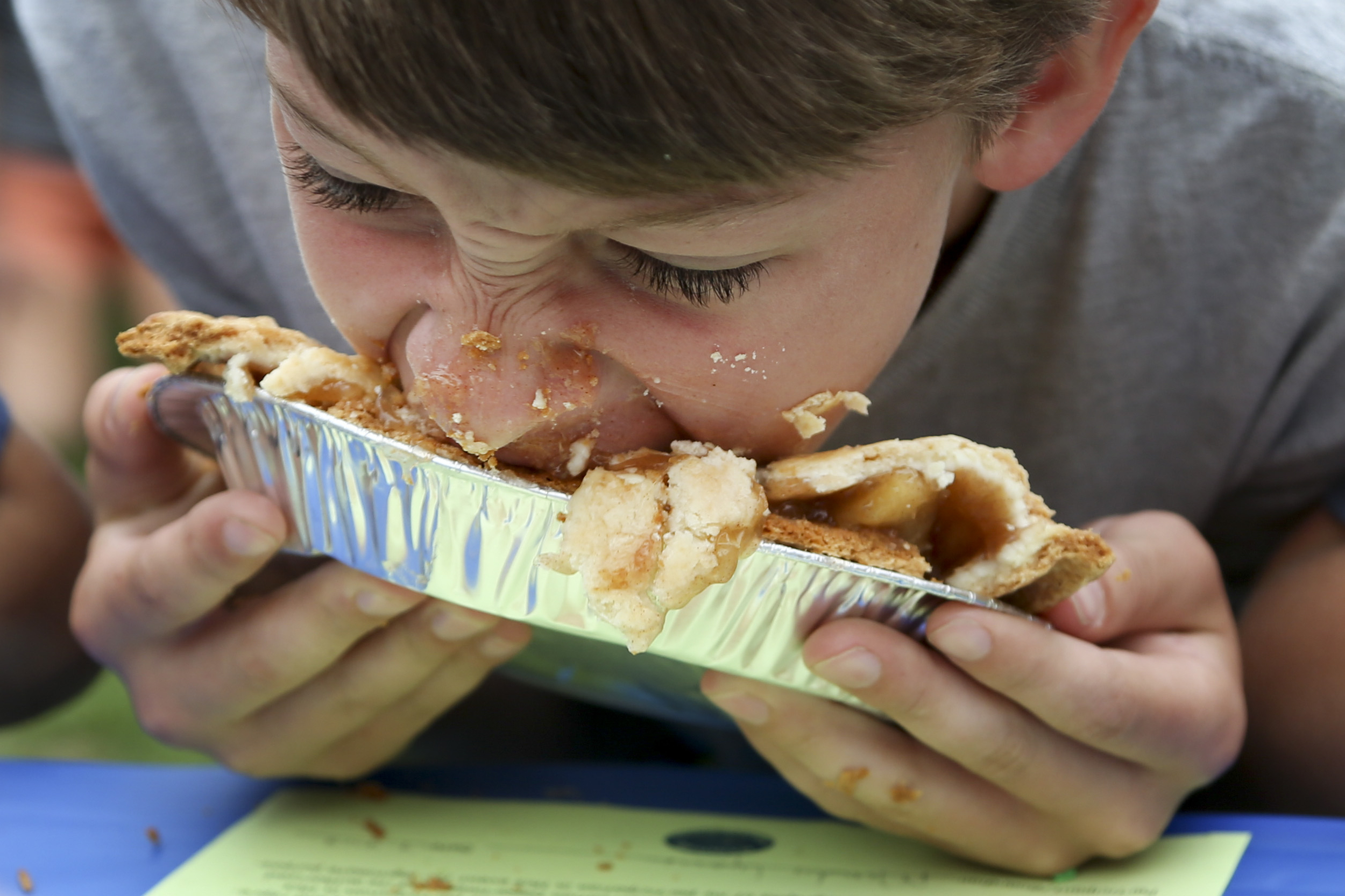 Billy Lyons, 11, of Hanover, N.H., competes in the pie-eating competition on the Dartmouth green in Hanover, N.H., on Saturday, July 4, 2015. Billy's older brother Tom, 12, won this year's ages 12 and under competition.