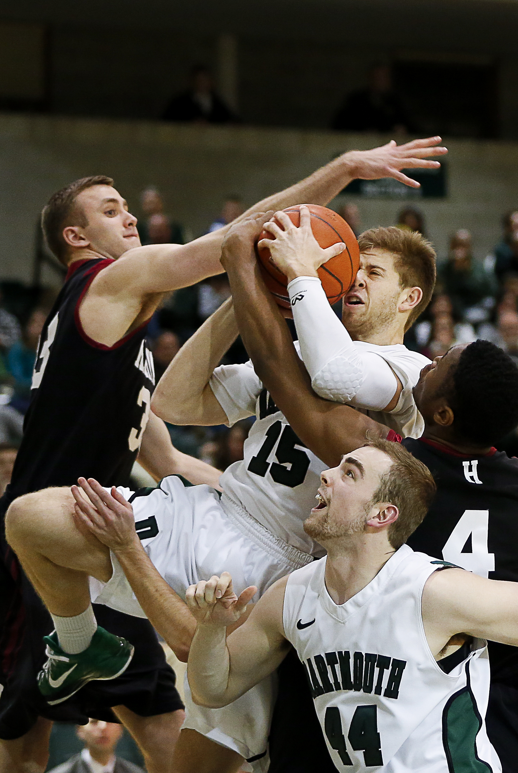 Dartmouth's Kevin Crescenzi, center, struggles to make a layup while Harvard's Evan Cummins, left, defends during the game in Hanover, N.H., on Jan. 10, 2015. Harvard won 57-46.