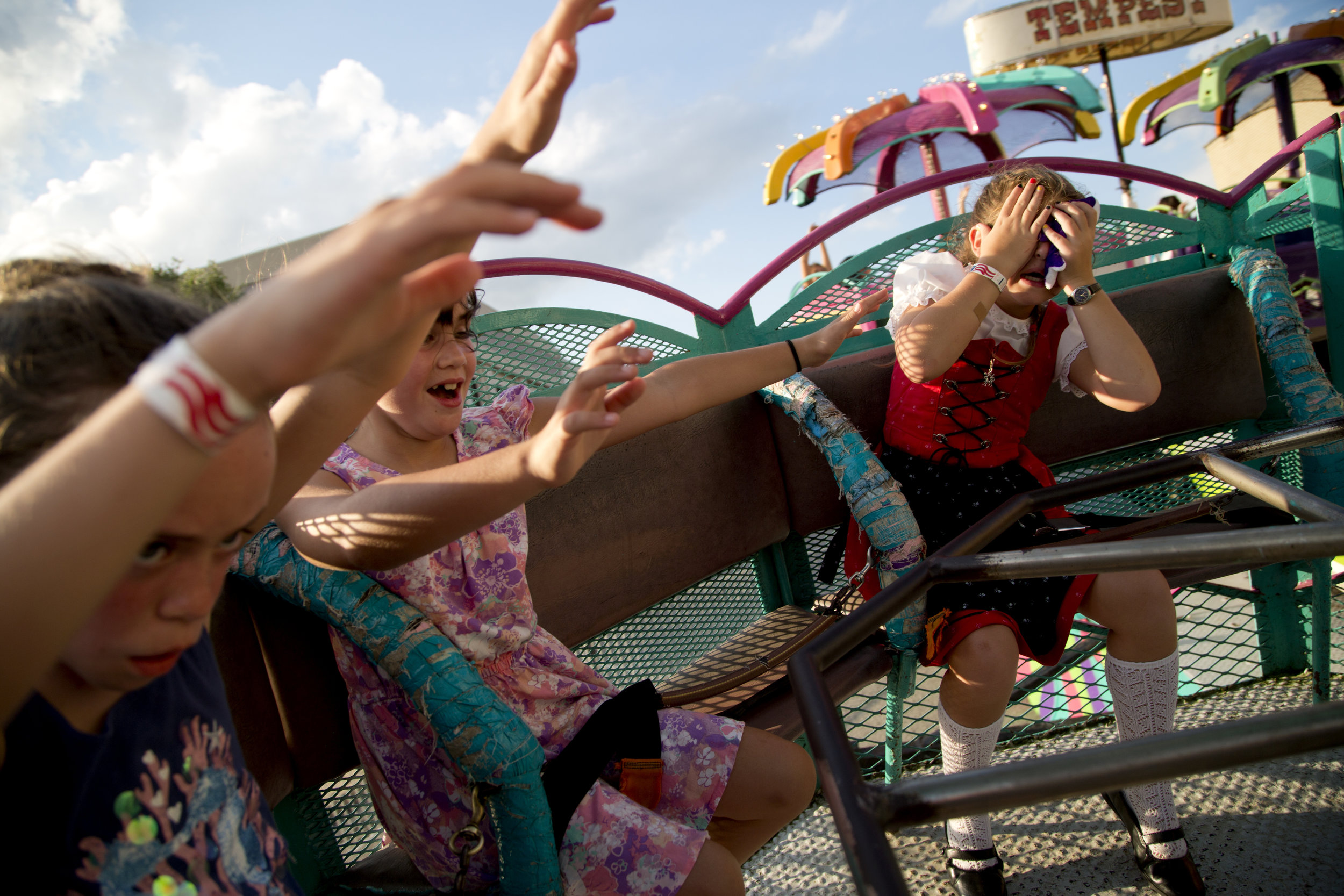 Little Miss Strassenfest Kennedy Kunkel of Jasper, 8, right, covered her eyes after getting dizzy on the Tempest carnival ride during Strassenfest in Jasper on Saturday. Ava Claire Werne of Jasper, 8, left, and Tessa Werne of Jasper, 7, tried to keep their hands in the air for the entire ride.