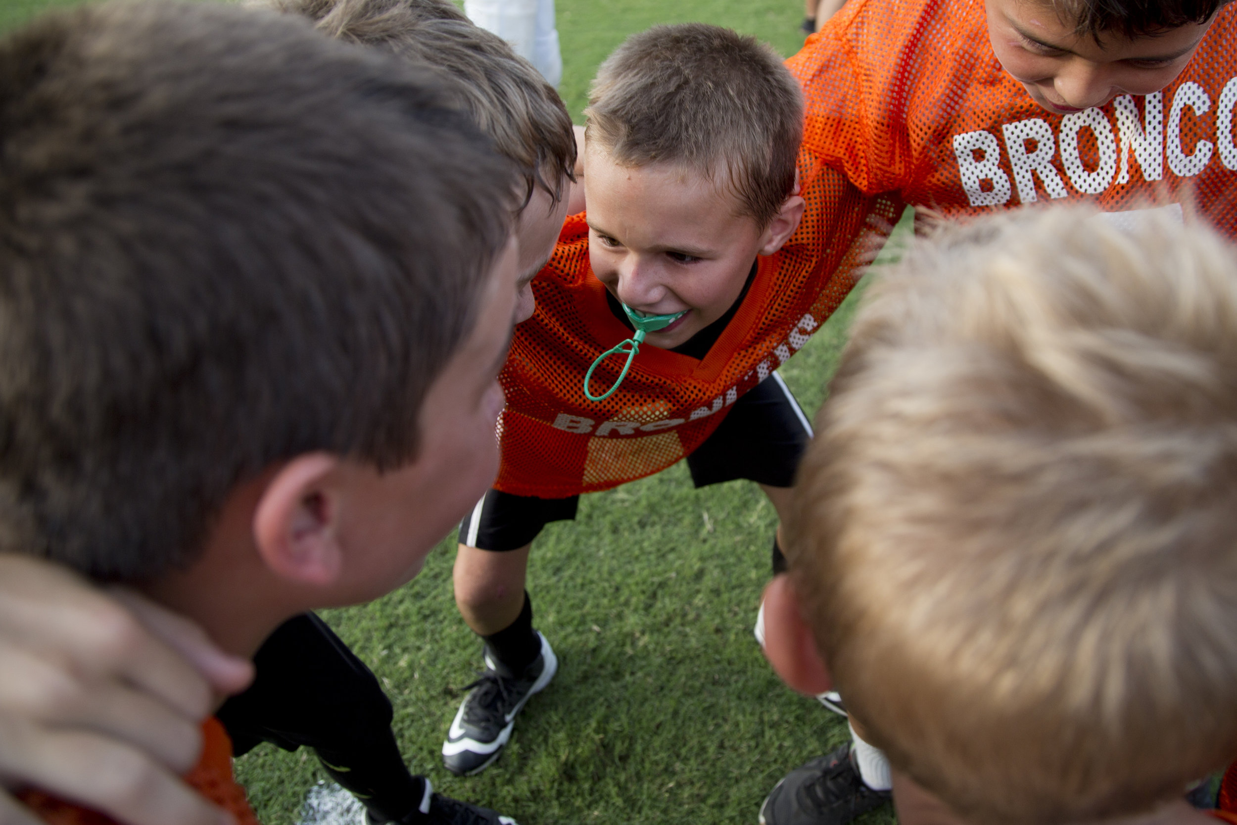 Kaden Meunier of Ferdinand, 9, center, huddled with his new Broncos teammates during SP&F Flag Football Draft Day at Ranger Field in Ferdinand on Wednesday. Over 50 second-, third-, and fourth-graders were drafted onto six different flag football teams.