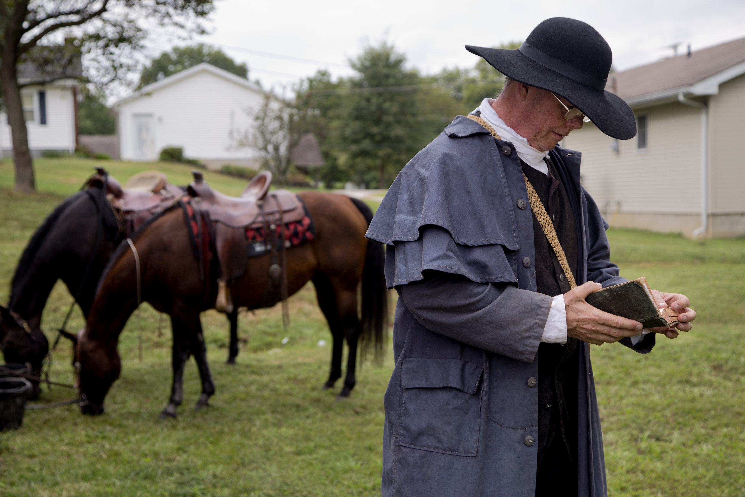 Mike Mulligan of Waxhaw, N.C., thumbed through his bible before preaching at the Cowboys for Christ event at Christ Community Fellowship Church in Huntingburg on Saturday. Mulligan and Calvin Barfield of Conway, S.C., travelled to Huntingburg with their horses, Honey and Sassy, to give rides to kids and preach about Jesus.