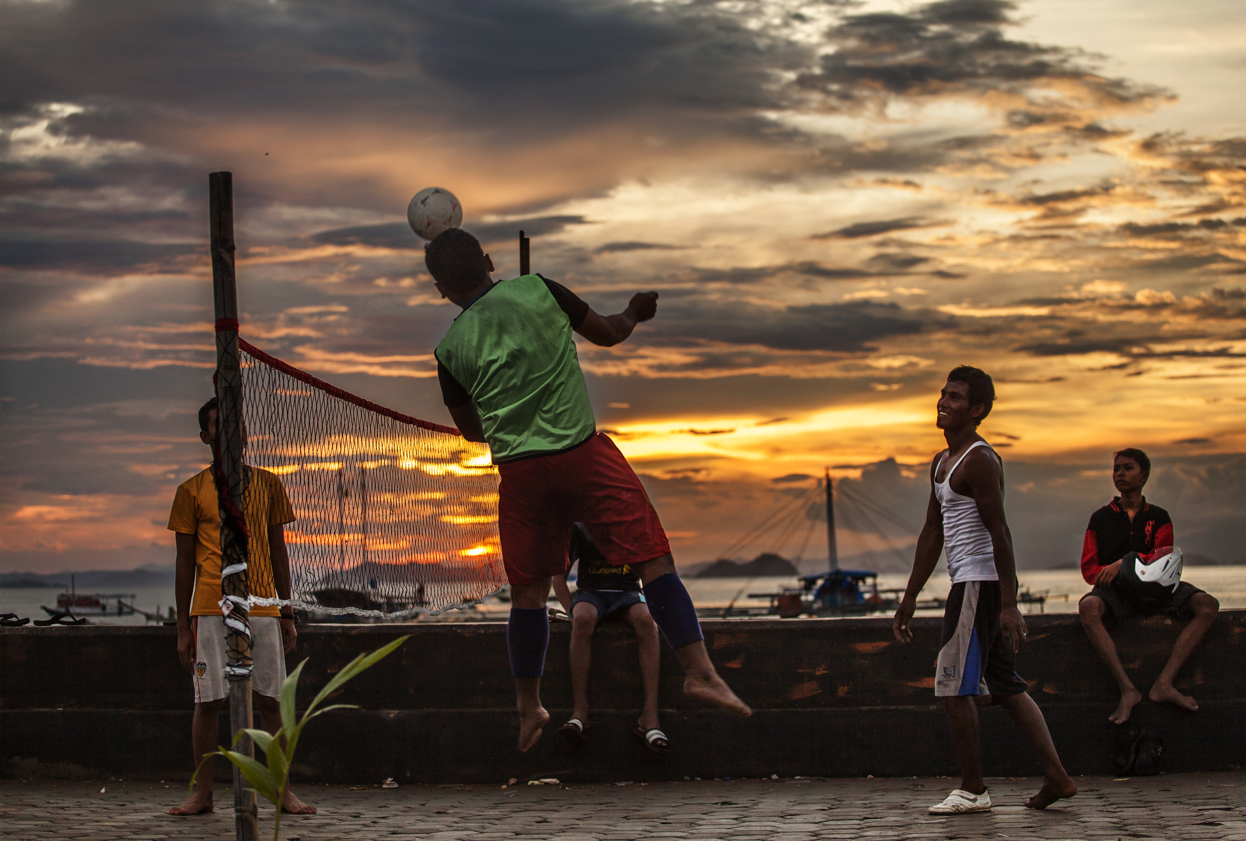 Guys playing hand and leg volleyball ( I have no idea what this game is called) in Labuan Bajo