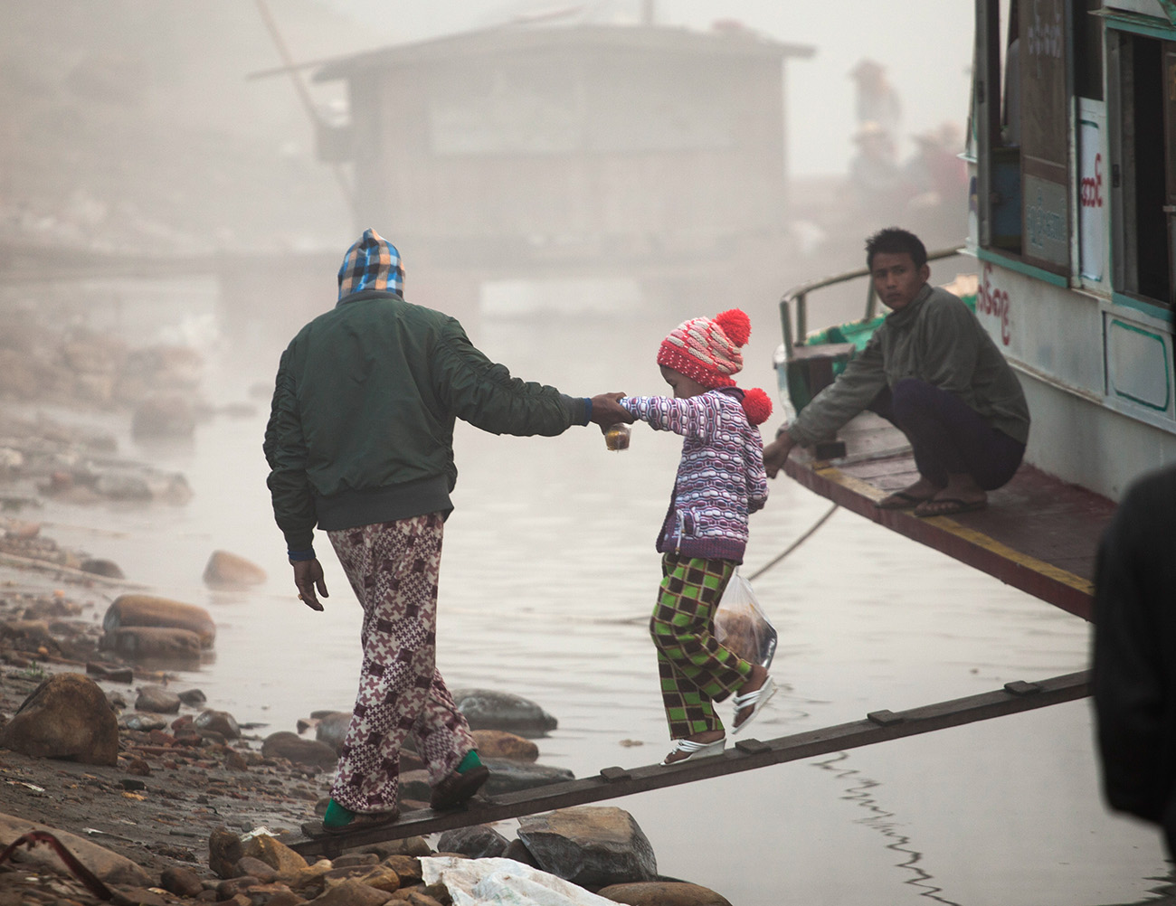 Dad helps his daughter off the boat, Katha
