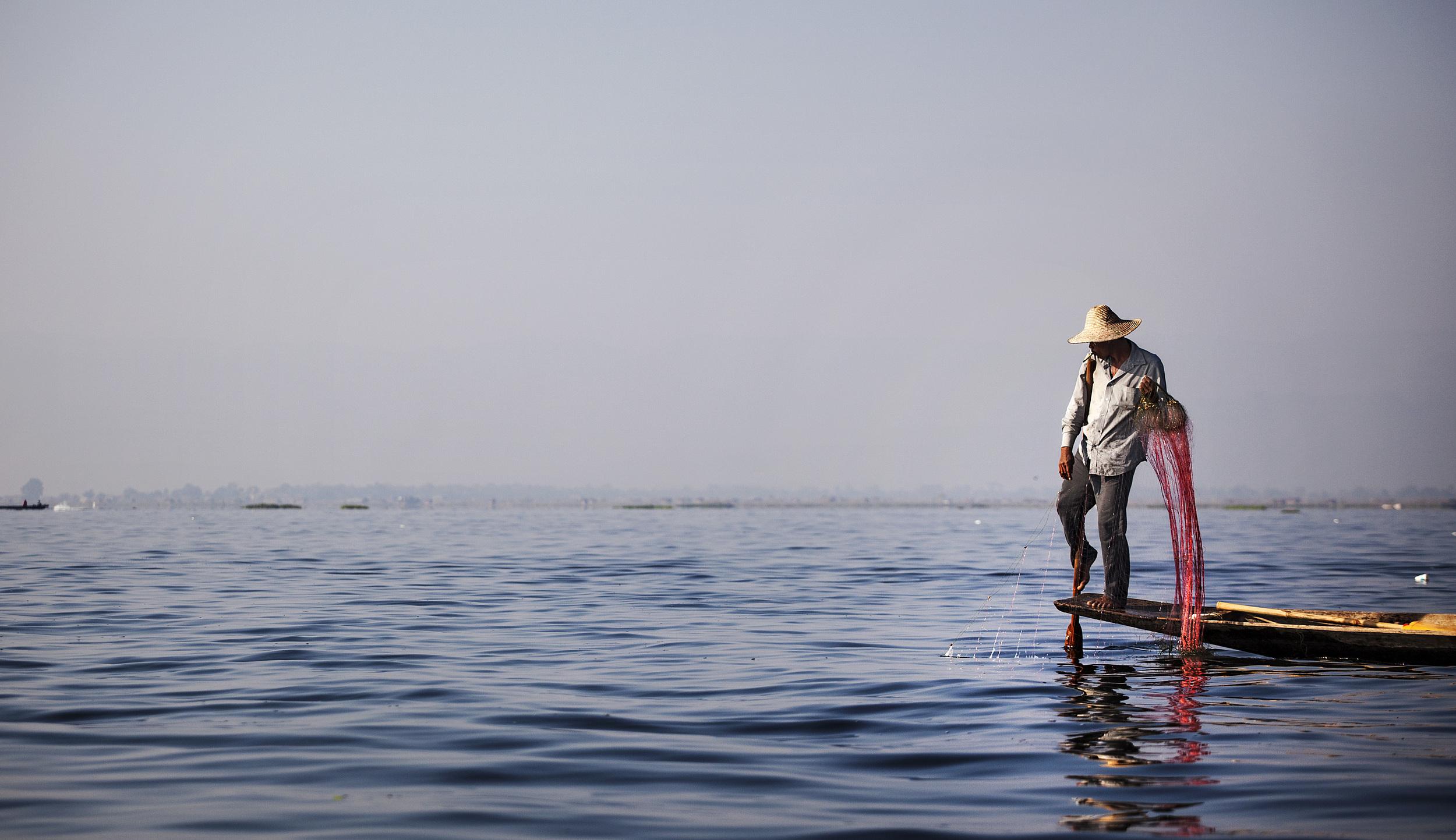 fisherman using the distinctive one legged paddling technique