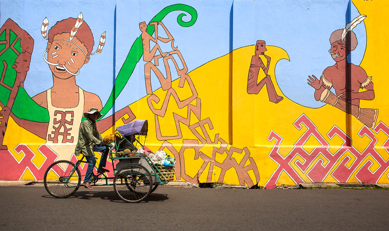 3 wheeled bicycle taxi, called a becak, drives by a mural in Surabaya