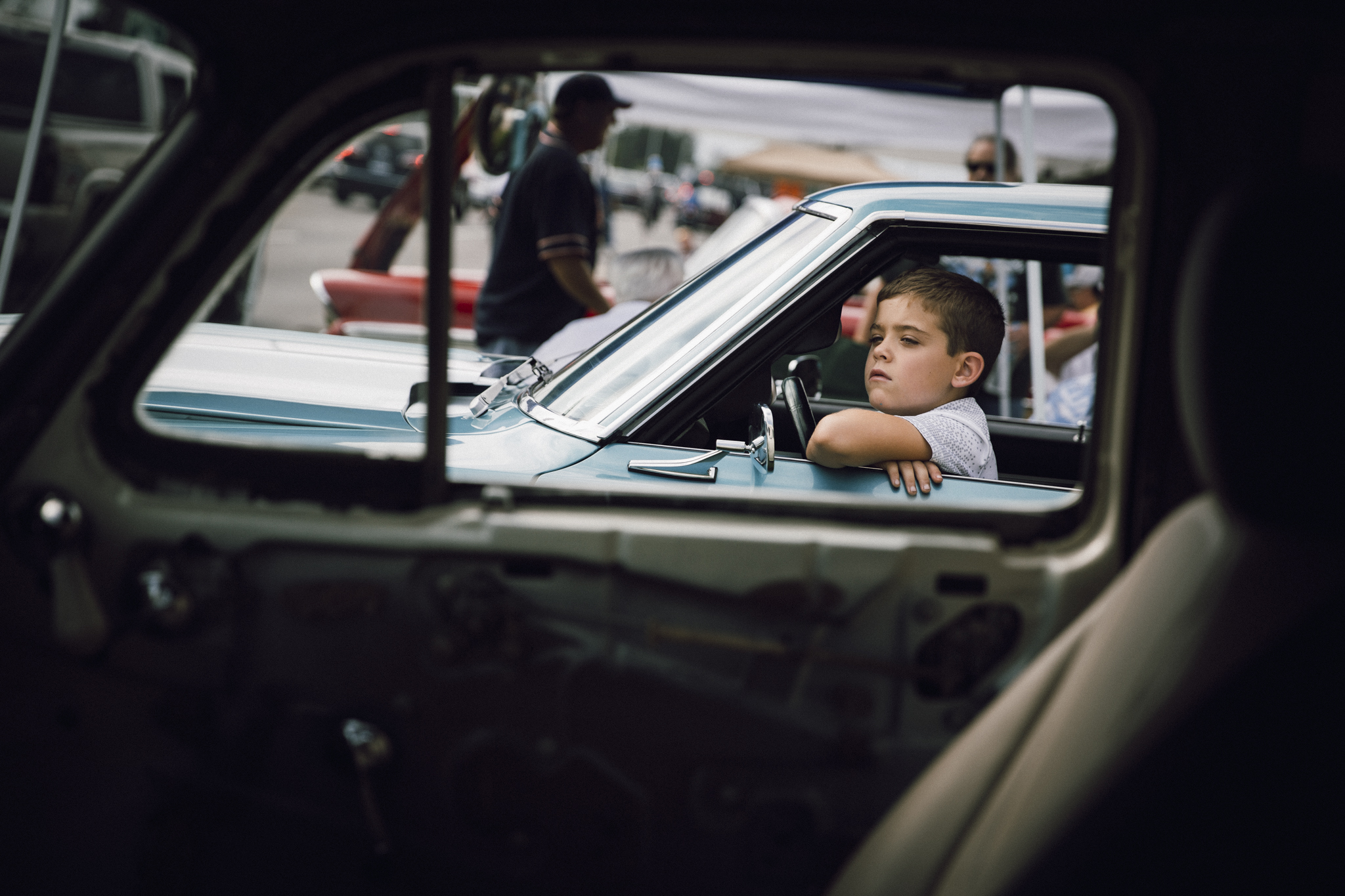 "After photographing this boy at Dream Cruise, I walked up to him and asked which car was his favorite. He looked up at me, patted the door and said, ""this one."""