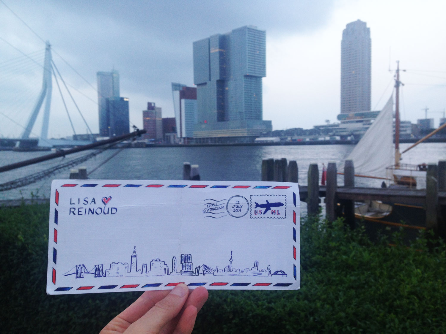 A LAURA ANN custom illustrated wedding invitation of the NYC-Rotterdam skyline, pictured here on site at the wedding reception, the ' De Maas ' Rotterdam yacht club, featuring the stunning Rotterdam skyline from the back terrace.