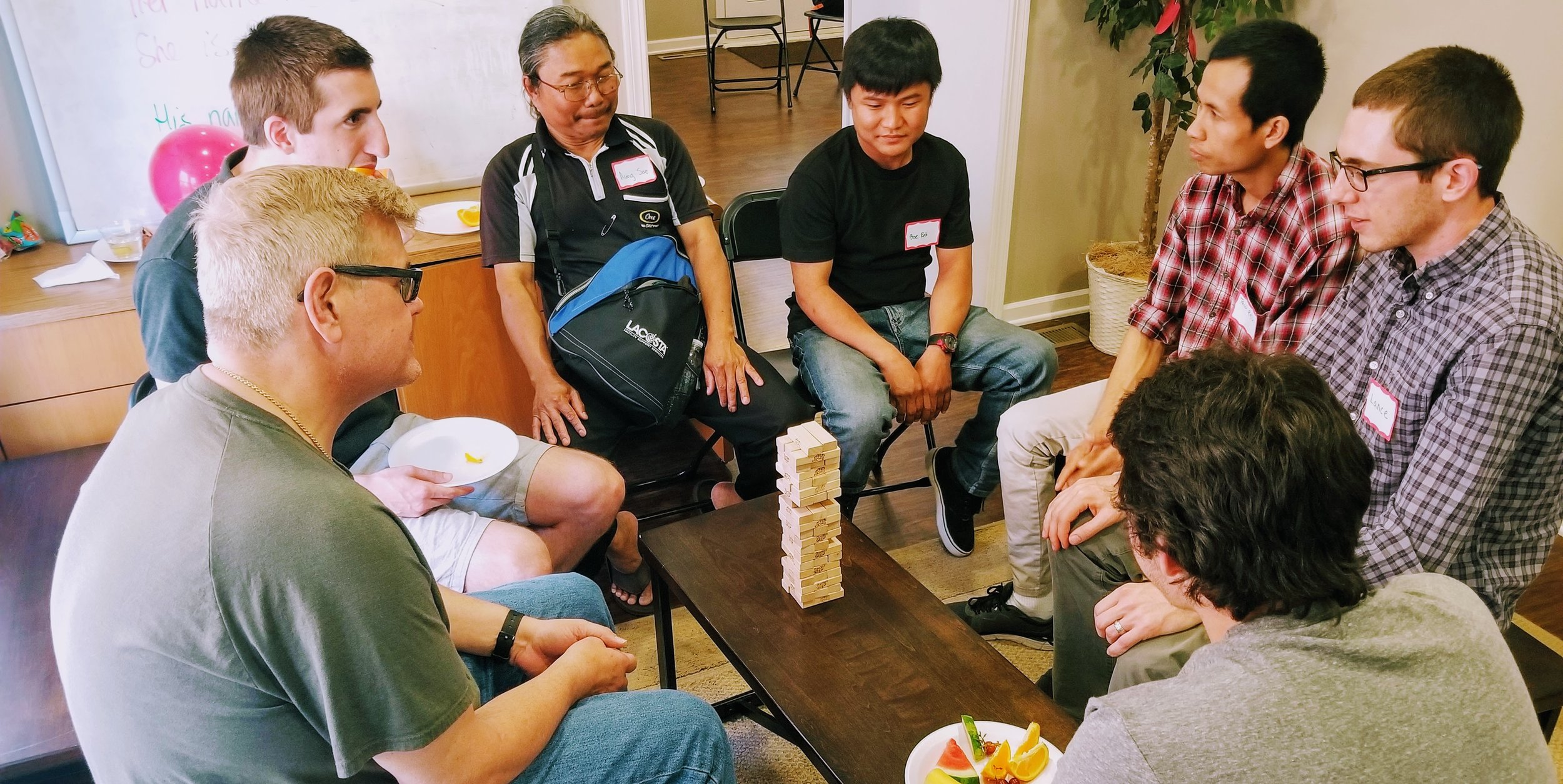 English Club participants practice English as they enjoy a game of Jenga.