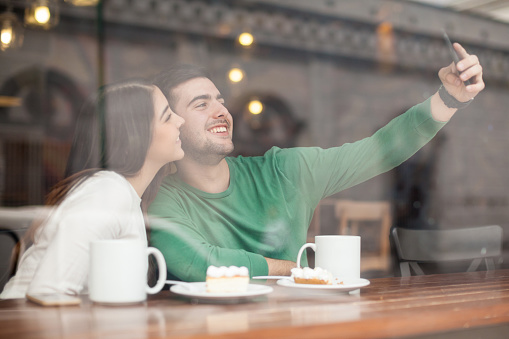 Cute couple taking a picture in your business, and posting out to their world