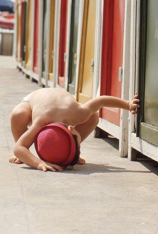 Very young girl [Bettina] peeking underneath a cabana
