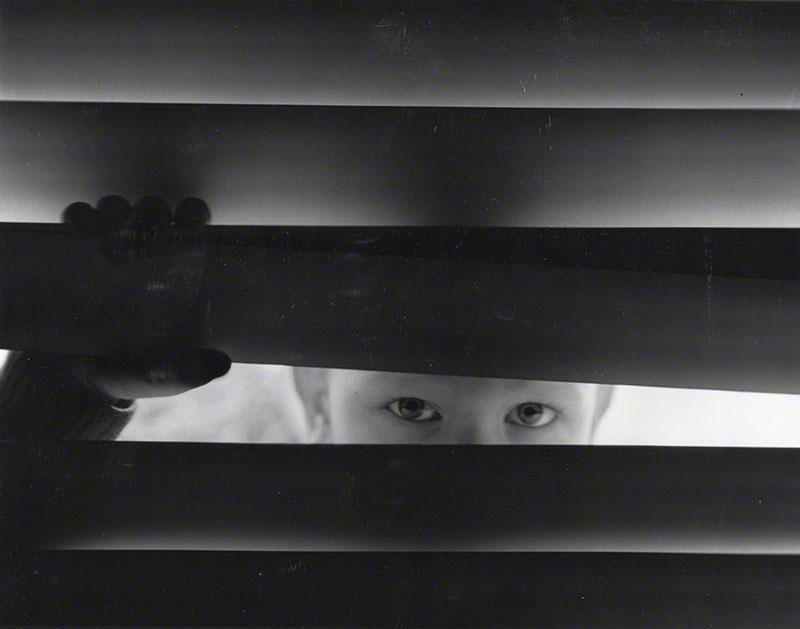 Roberto looking through Venetian blinds