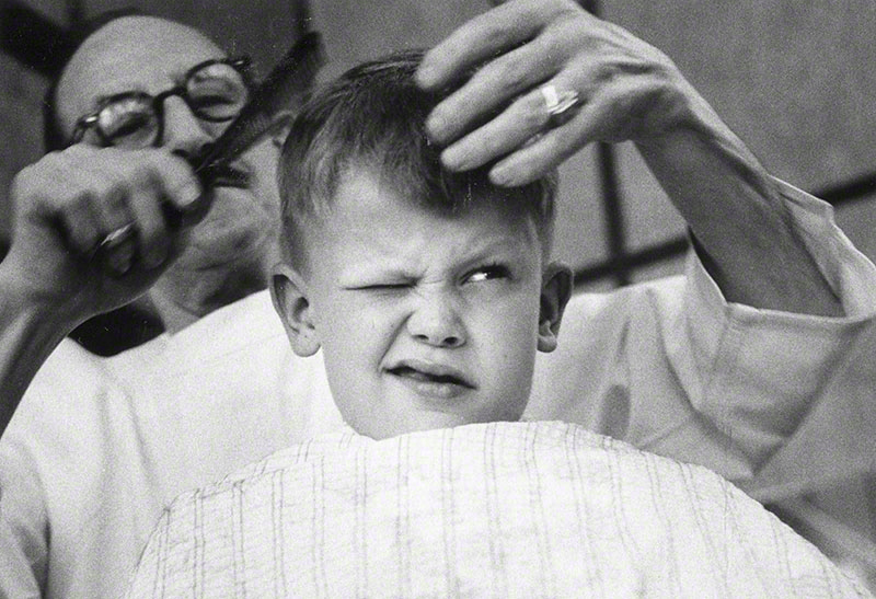 Roberto getting haircut from neighborhood barber