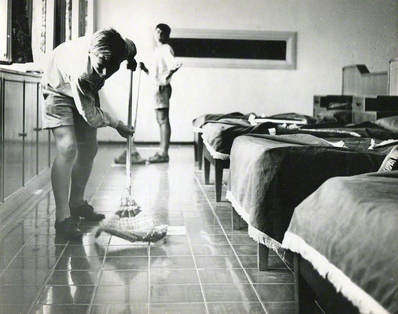 Two boys polishing the floor of a dormitory room