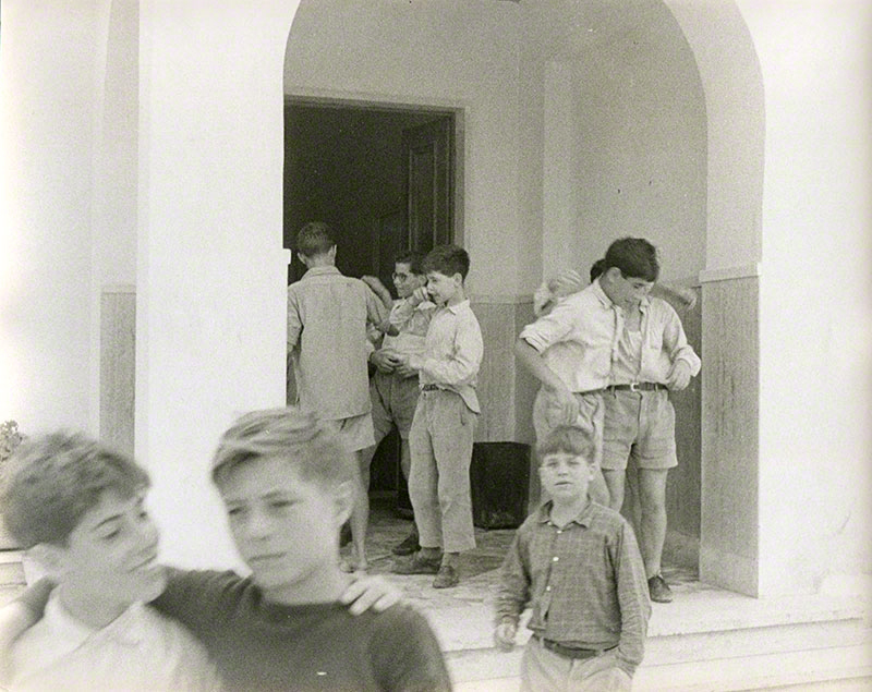 Group of boys milling around an entrance to the school
